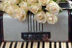 葡萄酒手风琴和白玫瑰花束  怀乡音乐的概念 免版税图库摄影