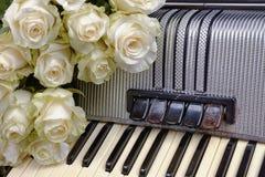 葡萄酒手风琴和白玫瑰花束  怀乡音乐的概念 免版税库存图片