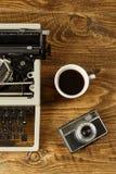 葡萄酒打字机、咖啡和在木桌a上的一台照相机 免版税库存图片