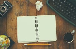葡萄酒打字机、空白的笔记本、咖啡和在木桌上的老照相机顶视图照片  减速火箭的被过滤的图象 免版税库存照片