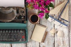 葡萄酒打字机、空白的笔记本、咖啡和在木桌上的老风船的图象 库存图片