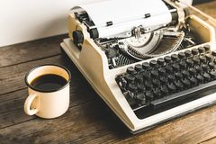 葡萄酒打字机和一个杯子在木表上的热的咖啡 Jo 免版税库存图片