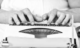 葡萄酒打字机概念 键入减速火箭的书写机器的手 老打字机和作者手 男性手类型故事 免版税库存照片