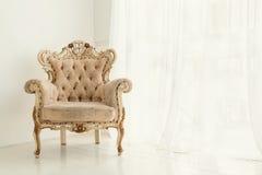 葡萄酒扶手椅子对白色墙壁和窗口 免版税库存照片