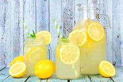 葡萄酒投手与金属螺盖玻璃瓶玻璃的柠檬水在土气蓝色木头 免版税库存照片