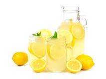 葡萄酒投手与金属螺盖玻璃瓶玻璃的柠檬水在白色 库存图片
