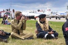 葡萄酒拍与照相机的飞行员制服的人照片与瑞士Pilatus Warbird特技队P3飞行物在背景中 免版税图库摄影