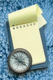 葡萄酒指南针和空白的黄色笔记薄 免版税库存图片
