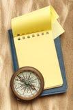 葡萄酒指南针和空白的黄色笔记薄 库存照片