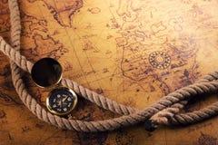 葡萄酒指南针和绳索在旧世界映射 库存照片