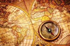 葡萄酒指南针在一张古老世界地图说谎。 免版税库存照片