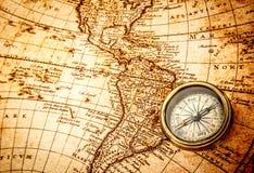 葡萄酒指南针在一张古老世界地图说谎 库存照片