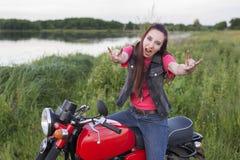 葡萄酒摩托车的一个女孩显示一个山羊标志户外 免版税图库摄影