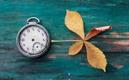 葡萄酒时钟和秋天在木背景生叶 免版税库存图片