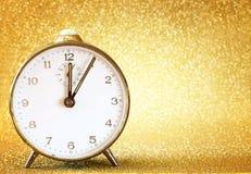 葡萄酒时钟有闪烁的金黄背景 免版税库存图片