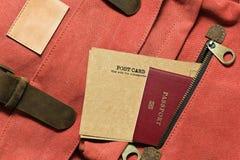 葡萄酒明信片和护照在背包的口袋 免版税图库摄影