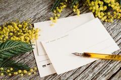 葡萄酒明信片嘲笑与黄色花含羞草和葡萄酒笔墨水在灰色木背景 免版税库存图片