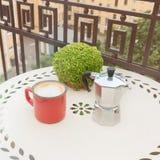 葡萄酒有咖啡壶的咖啡杯特写镜头在户外阳台的白色桌上 免版税库存图片