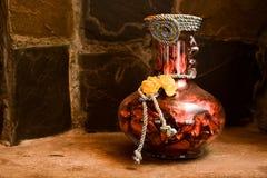 葡萄酒有干玫瑰花瓣的花瓶 库存照片
