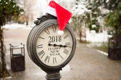 葡萄酒有文本新年快乐2018年和圣诞老人帽子的街道时钟在他们在公园在冬天 免版税库存照片