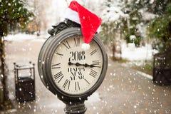 葡萄酒有标题的新年快乐街道时钟2018年和在他们的圣诞老人帽子与落的雪花 图库摄影