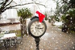 葡萄酒有标题的新年快乐街道时钟2018年和在他们的圣诞老人帽子在多雪的公园 免版税库存图片
