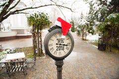 葡萄酒有标题的新年快乐街道时钟2018年和在他们的圣诞老人帽子在镇公园 免版税库存图片