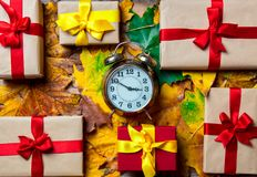 葡萄酒有节日礼物的闹钟和槭树叶子 免版税库存照片