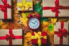 葡萄酒有节日礼物的闹钟和槭树叶子 免版税库存图片