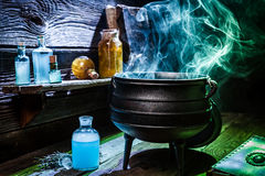 葡萄酒有蓝色烟的witcher大锅和魔药为万圣夜 图库摄影