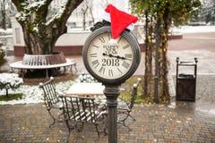葡萄酒有题字新年快乐2018年和圣诞老人帽子的街道时钟在他们在冬天公园 库存照片