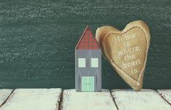葡萄酒木五颜六色的房子和织品心脏的图象在木桌上在黑板前面 退色的减速火箭的被过滤的图象 图库摄影
