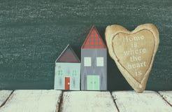 葡萄酒木五颜六色的房子和织品心脏的图象在木桌上在黑板前面 退色的减速火箭的被过滤的图象 免版税库存图片