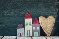 葡萄酒木五颜六色的房子和织品心脏的图象在木桌上在黑板前面 免版税库存照片