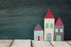 葡萄酒木五颜六色的房子的图象在木桌上的在黑板前面 图库摄影