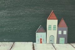 葡萄酒木五颜六色的房子装饰的图象在木桌上的在黑板前面 退色的减速火箭的被过滤的图象 免版税库存图片