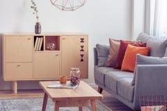 葡萄酒木咖啡桌和洗脸台在典雅的客厅内部与灰色长沙发 图库摄影