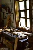 葡萄酒木图画书桌在窗口的木匠车间 免版税库存图片