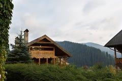 葡萄酒木房子在旅游中心依靠与桦树、秋天草和植物 Alpain风景  图库摄影