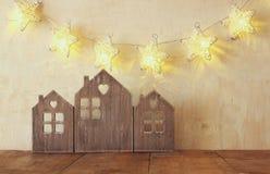 葡萄酒木房子装饰的低调图象在木桌和星诗歌选上的 被过滤的减速火箭 选择聚焦 免版税库存照片