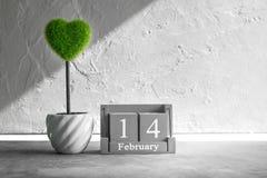 葡萄酒木日历与绿色心脏的2月14日在木头t 图库摄影
