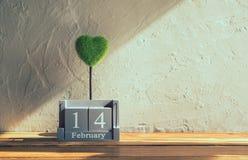 葡萄酒木日历与绿色心脏的2月14日在木头t 库存图片
