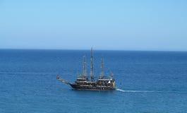 葡萄酒木老船在蓝色海 免版税库存照片