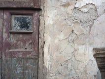 葡萄酒木肮脏的门,与与未洗的玻璃的一个小窗口在一个土气房子的白色墙壁上,有落的膏药的, 库存照片