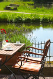 葡萄酒木表和椅子在水边 图库摄影