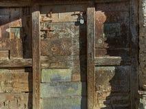葡萄酒木门,由棕色和绿色委员会做成,关闭在老挂锁,油漆在表面剥落了并且创造美丽 库存照片