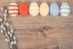 葡萄酒杨柳的照片、枝杈和五颜六色的复活节彩蛋包裹了在土气板,文本的拷贝空间的羊毛串 库存照片