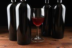 葡萄酒杯和四个瓶 库存图片