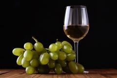葡萄酒杯和葡萄在木桌上 库存照片