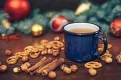 葡萄酒杯热的茶用在用杉木装饰的木背景的薄脆饼干 库存照片